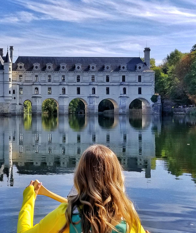 Jeune femme dans un canoe en face du chateau de chenonceau